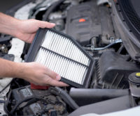mechanic holding a car air filter over an engine